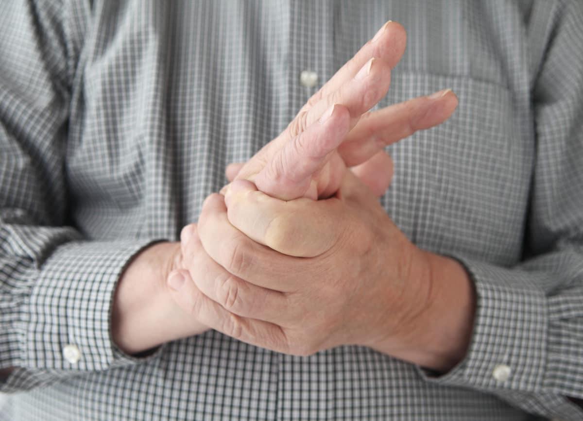 man rubbing hands in pain
