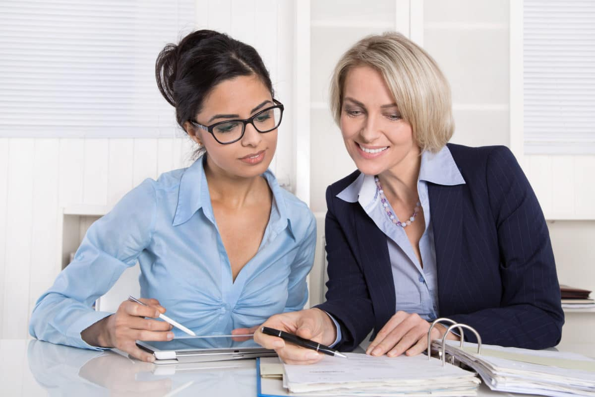 employee and employer talking at desk