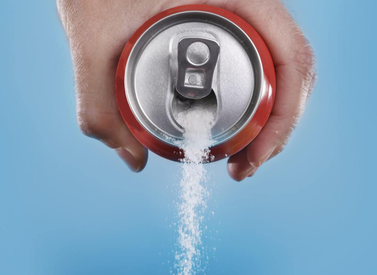 hand holding soda can pouring out sugar