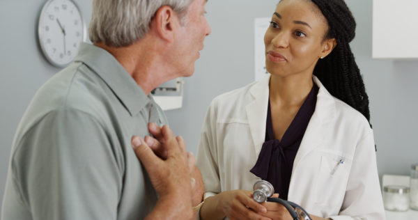 Young black female doctor talks to patient who is experiencing chronic pain