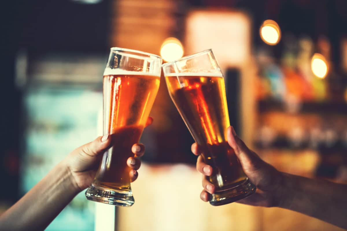 2 friends clinking beer glasses together